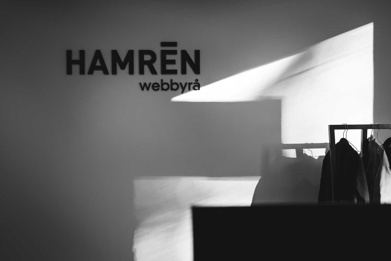"""Foto Hamrén kontor. Svartvitt bild av vit vägg där """"Hamren Webbyrå"""" står på väggen"""