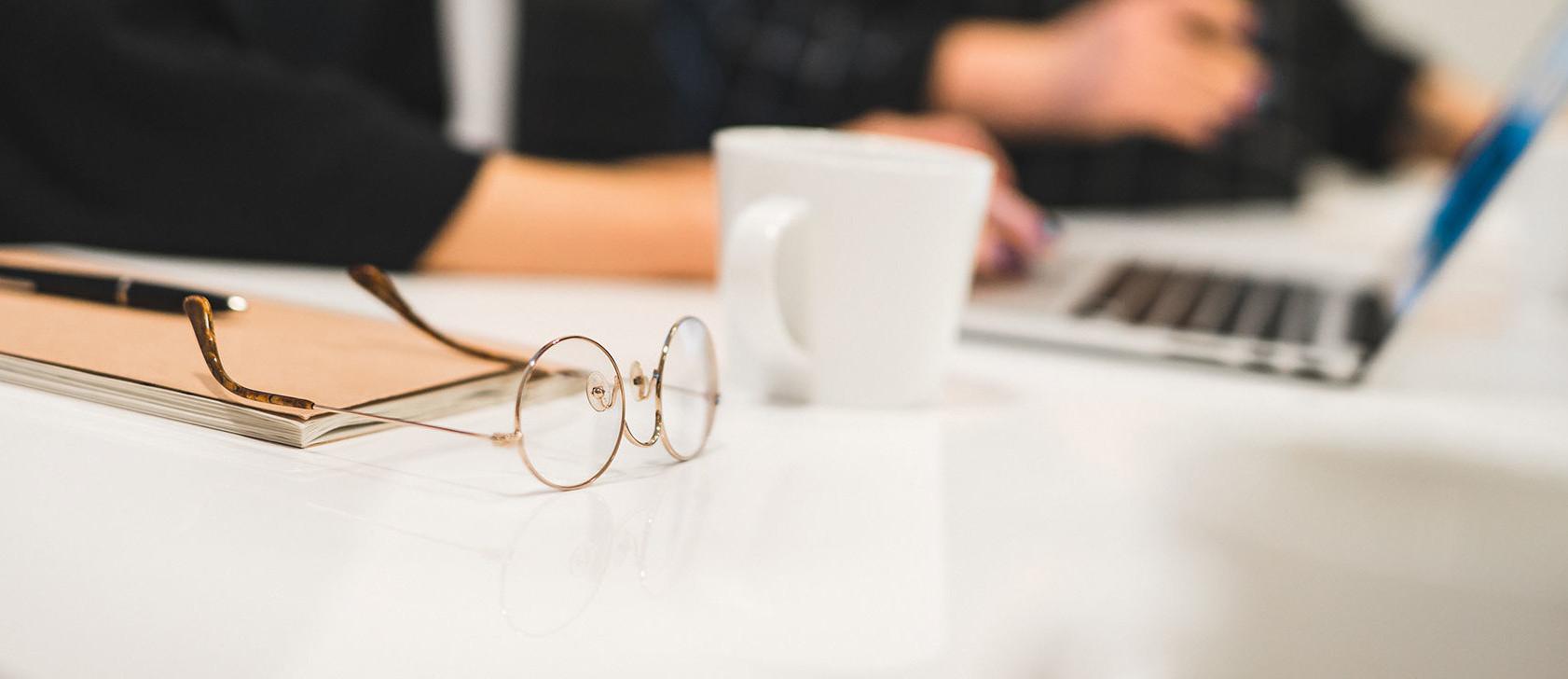Ett par runda glasögon ligger på ett bord. I bakgrunden arbetar två personer på sina datorer.