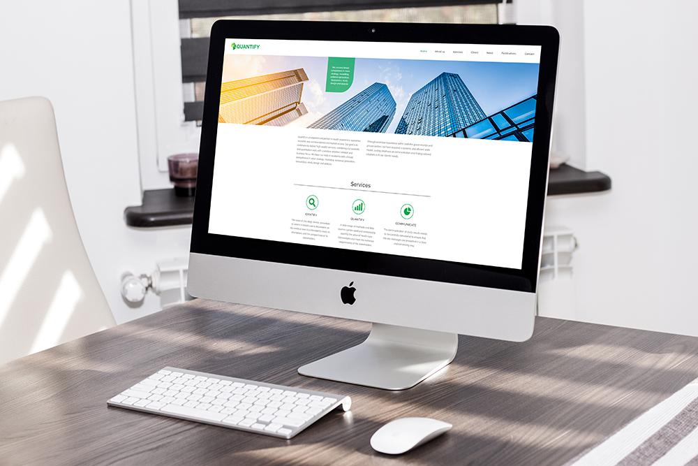 Quantify Researchs hemsida på en stationär Mac-dator. Hemsidan är ljus med gröna detaljer. Högst upp syns byggnader underifrån, med solstrålar som kommer in från vänster.