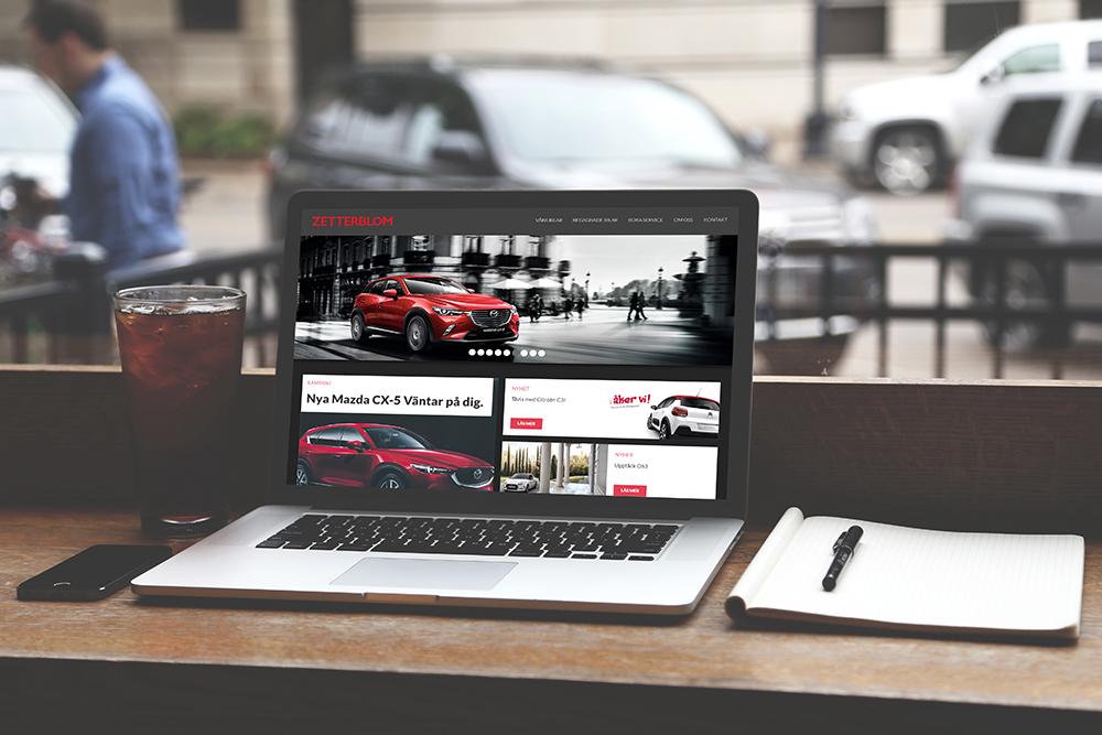 Zetterblom bils hemsida på en laptop i en cafémiljö. Datorn är i fokus, bakgrunden är suddig. På sidan av laptopen ligger ett anteckningsblock.