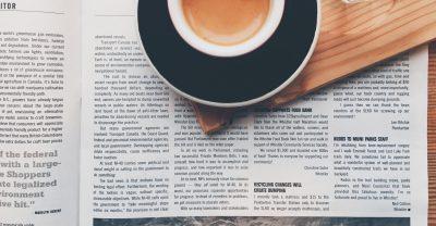 En tidning med ett tydligt grid ligger på ett bord. Ovanpå tidningen skymtar en kopp kaffe.