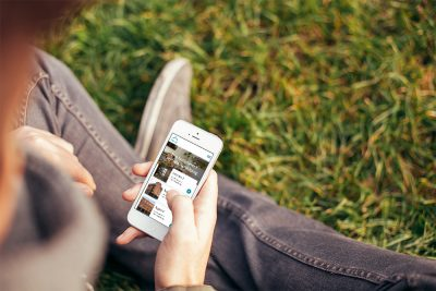Person sitter i gräset och kollar på hemsidan prio.se på telefonen