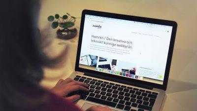 Hamrén webbyrås nylanserade hemsida syns över axeln på en person