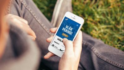 En person håller en smartphone i knät som visar startsidan på IFK Norrköpings nya hemsida